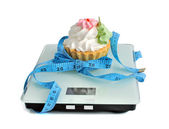 Cake on the scales measuring tape wrapped — Stock Photo