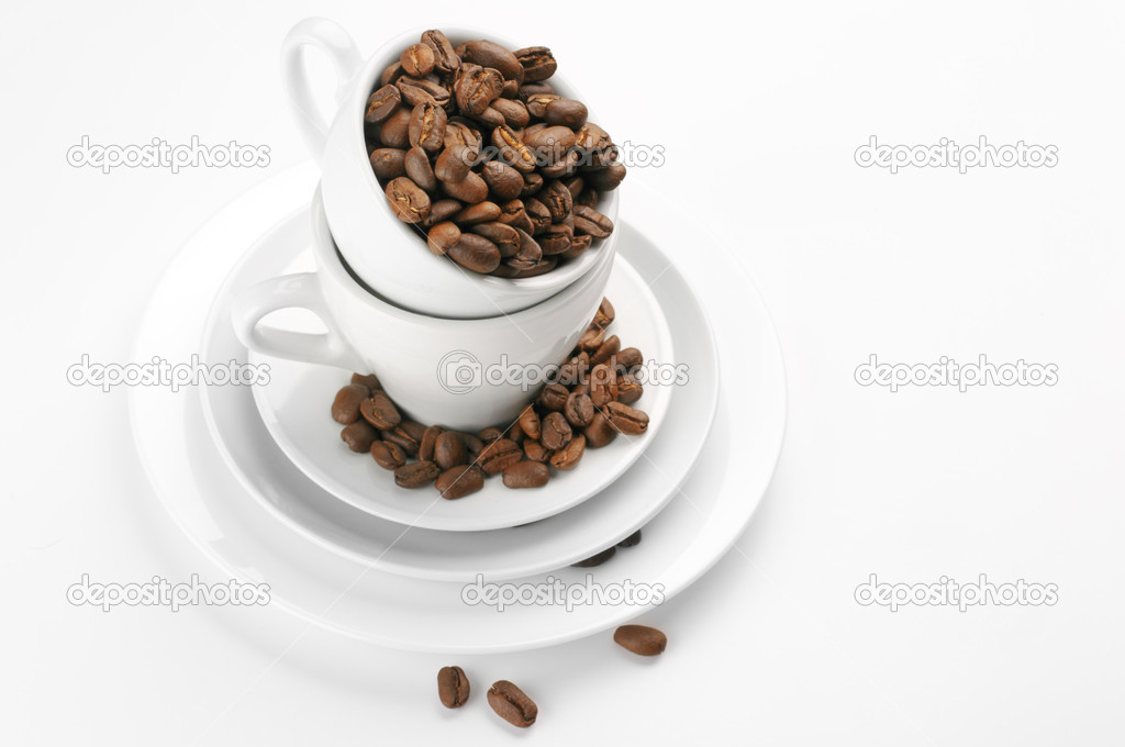 Roasted coffee beans in white cups on light background. — Stock Photo #8759922