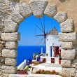 Windmill through an old window in Santorini island - Stock Photo