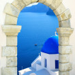 Traditional greek church through an old window in Santorini island, Greece — Stock Photo #9977175