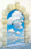 Seagull flying on blue sky through an old Venetian window — Stock Photo