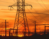 Electricity pylons at orange sunset — Stock Photo