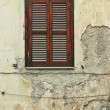 Stock Photo: Old shuttered window on dilapidated building