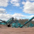 Making of crushed stone at stone quarry - Stock Photo