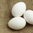 Three eggs on brown fabric texture - Stock Photo