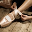 Ballet dancer tie up her pointes — Stock Photo #10234318