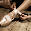 Stock Photo: Ballet dancer tie up her pointes