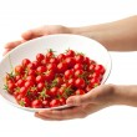 mano que sujeta la placa con tomates cherry frescos — Foto de Stock