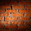 Aged brick wall illuminated with spotlight - Stock fotografie
