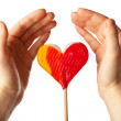 Hands surrounding lollipop heart - Stock Photo