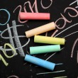 Colorful chalks on the blackboard - Stock Photo