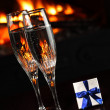 Glasses with champagne and a gift, fire as the background — Stock Photo