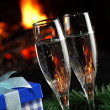 Glasses with champagne with christmas entourage, fire as the background — Stock Photo