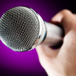 Microphone against the purple background - Stock Photo
