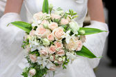 An image of a bride holding her bouquet of roses — Stock Photo