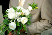 A bridegroom holding a bouquet of roses — Foto de Stock