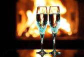 Blue glasses in front of fireplace — Stock Photo