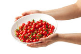 Hand holding plate with fresh cherry tomatoes — Stock Photo