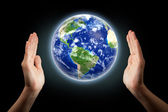 Hands around globe — Stock Photo