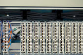 One busy switchboard panel and multitude of empty telephone panels — Stock Photo