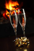 Glasses with champagne with golden bow, fire as the background — Stock Photo