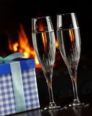 Champagne glasses and a gift — Stock Photo
