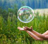 Captura de una burbuja de jabón de mano — Foto de Stock