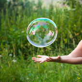 Hand catching a soap bubble — Stock Photo