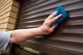 Hand cleaning roller shutters — Stock Photo
