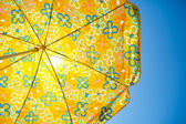 Beach umbrella against sunny blue sky — Stock Photo