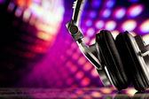 Headphones against purple disco background — Stock Photo