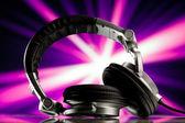 Fones de ouvido contra fundo roxo raios — Fotografia Stock