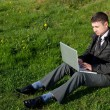 Man with a laptop on the grass — Stock Photo
