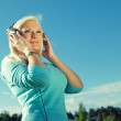 Young woman with headphones outdoors — Stock Photo