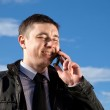Man on mobile phone on natural blue background — Stock Photo