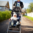 Happy father with baby son in stroller — Stock Photo