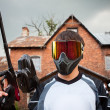 Stock Photo: Paintball shooter and house as background