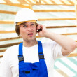 Builder on mobile phone - Stock Photo