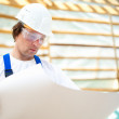 Builder manager looking at the construction plan - Stock Photo
