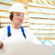 Builder seriously looking at the construction project — Stock Photo #10241905