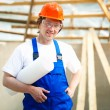 Stock Photo: Smiling builder holding construction plan