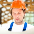 Builder looking at the construction plan — Stock Photo