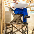 Builder sit on the wooden scaffolding — Stock Photo #10242002