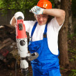 Tired worker holding a machine drill — Stock Photo #10242123