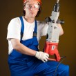 Worker holding a machine drill - Stockfoto