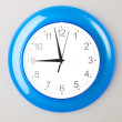 Blue office clock on grey wall — Stock Photo