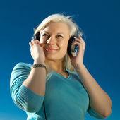 Młoda kobieta z słuchawkami na zewnątrz — Zdjęcie stockowe
