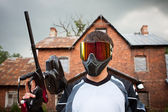 Paintball shooter and house as the background — Stock Photo