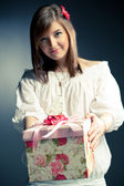 Beautiful girl makes a present, focus on the gift — Stock Photo