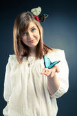 Beautiful girl holding a butterfly, focus on the butterfly — Stock Photo
